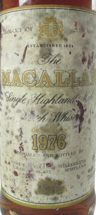 A damaged label on a Macallam whisky bottle