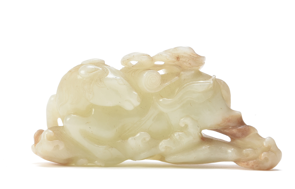 A Chinese pale celadon and russet jade carving of the 'Heavenly Horse', Tian Ma, Qing Dynasty, 18th century