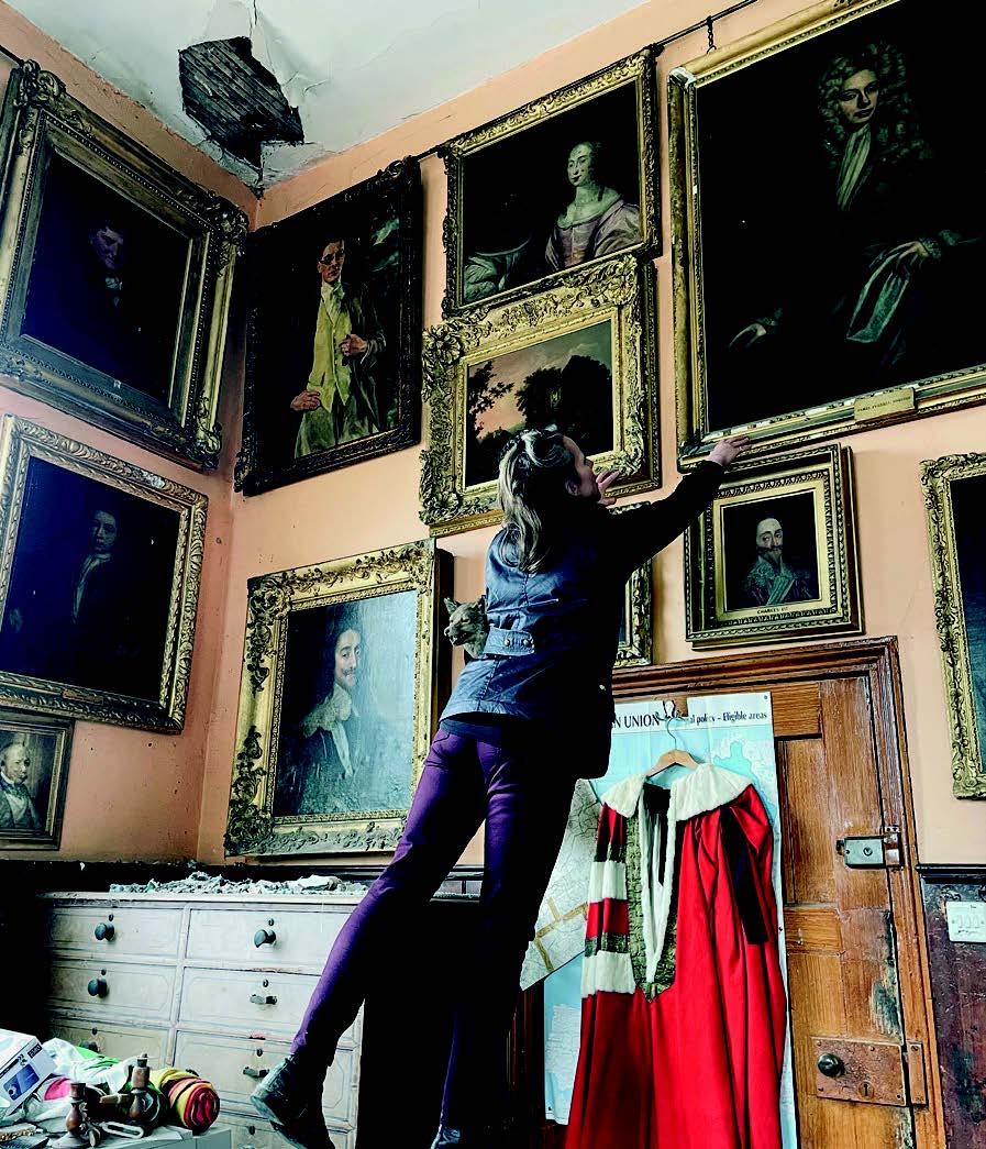 Christina Trevanion examines portraits on a wall
