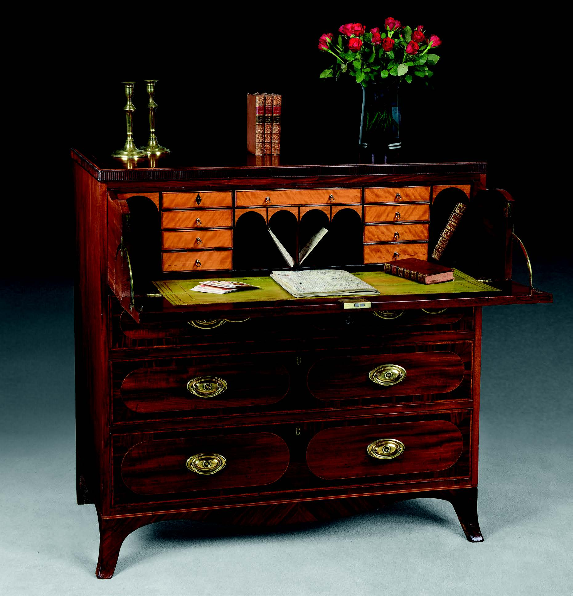 A Sheraton period mahogany secretaire chest of drawers, c. 1790, inlaid with obround panels on splayed bracket feet